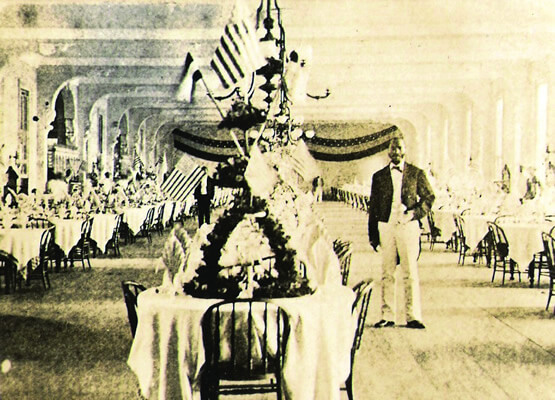 historic image of congress hall ballroom, man posed in front of American flags