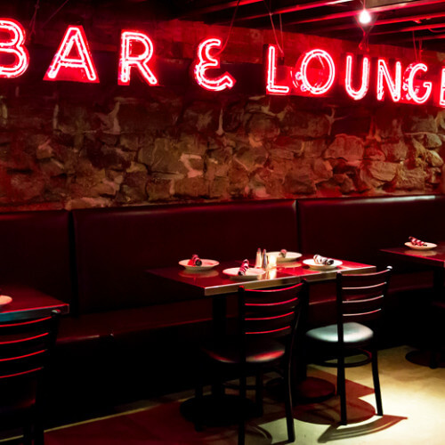 the boiler room tables chairs neon sign that reads bar and lounge