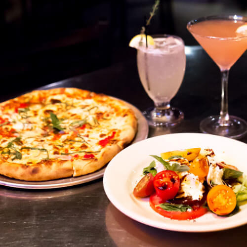 the boiler room pizza and caprese salad with cocktails