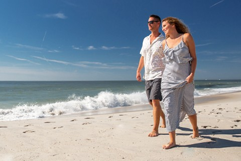 man and woman walking on beach