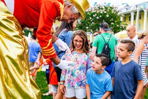 children having fun with magician at congress hall carnival