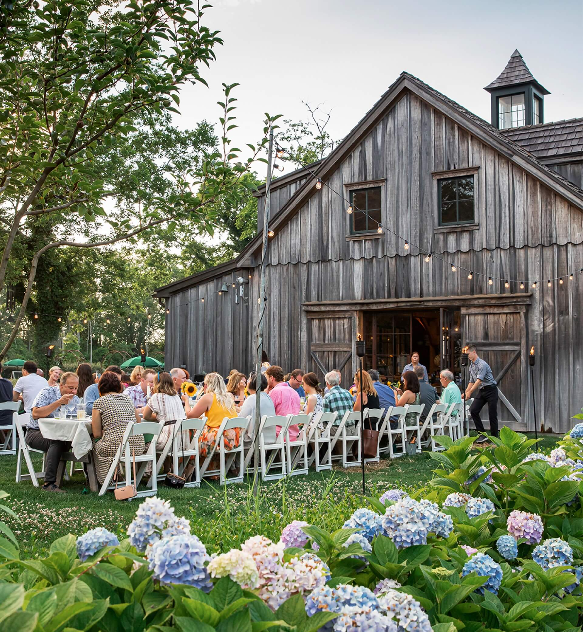 people eating at outdoor communal table outside beach plum farm barn