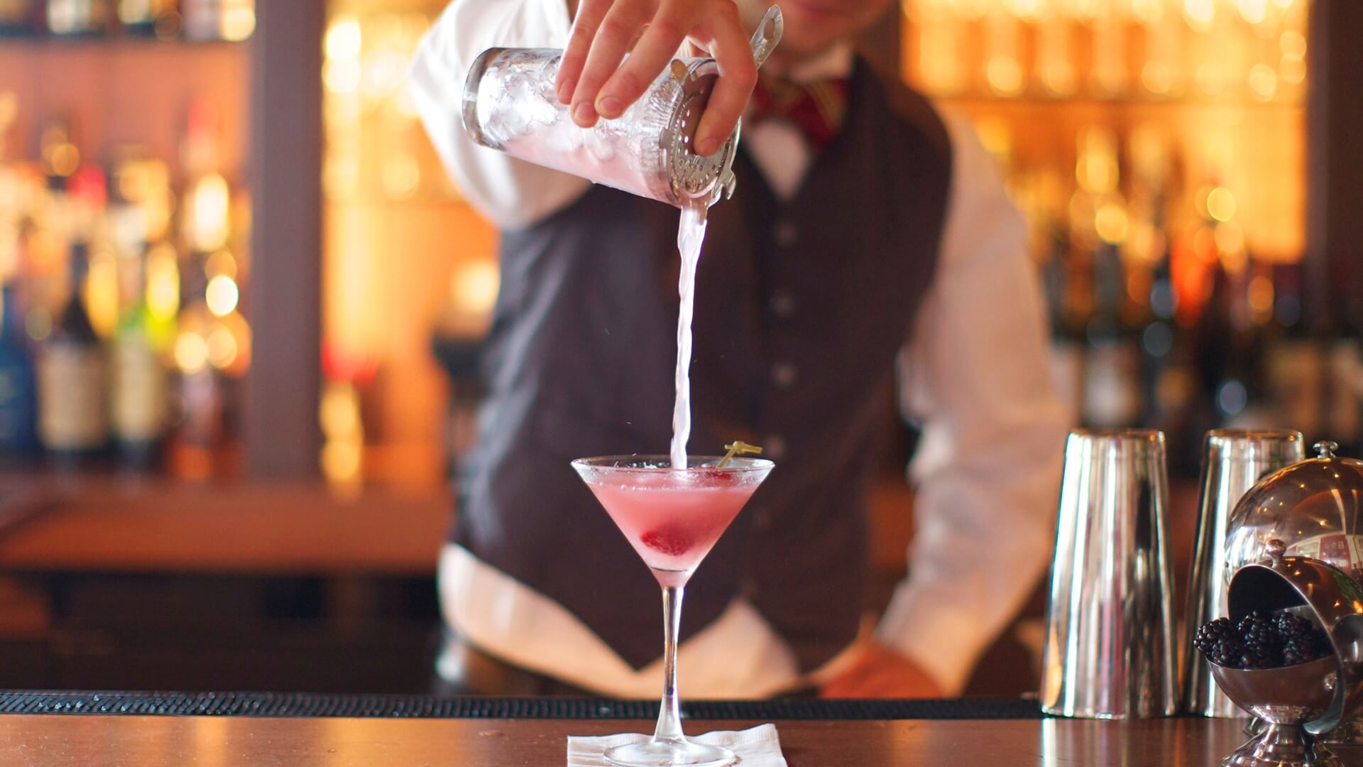 man pouring a cocktail at the ebbitt room bar