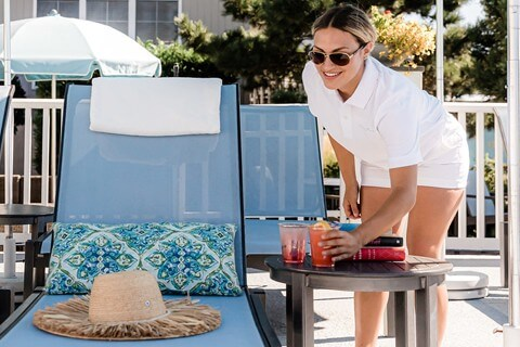 woman placing drinks down by a chair at the sandpiper pool