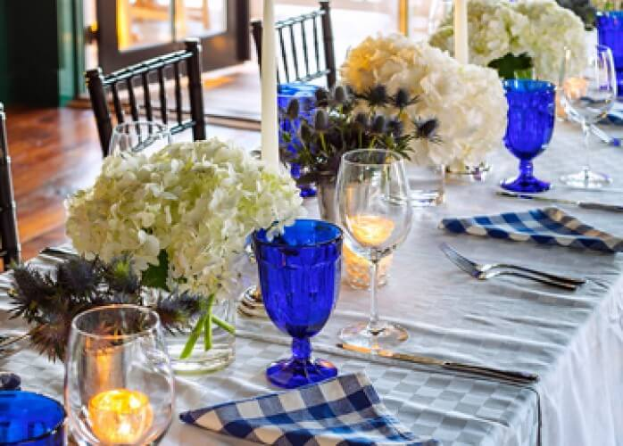 set table with blue glasses and flowers