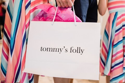 man holding bag that says tommys folly