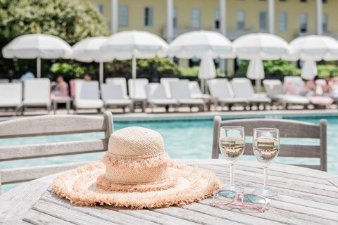 hat and wine glasses sitting by a pool