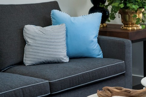gray couch with blue pillows